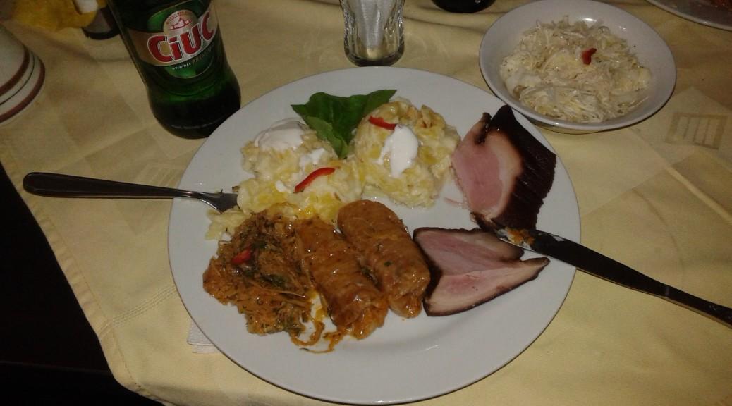 Pożegnalny obiad w Varzarii (i chyba największy). Wędzona golonka (ciolan afumat), ziemniaki ze śmietaną (rumuńska śmietana rządzi!) i sarmale...