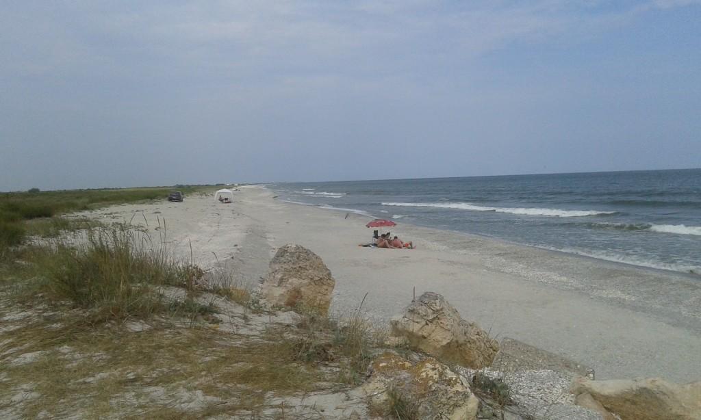 W polu widzenia widać zaledwie trzy grupki plażowiczów. W oddali majaczy jakiś większy kemping