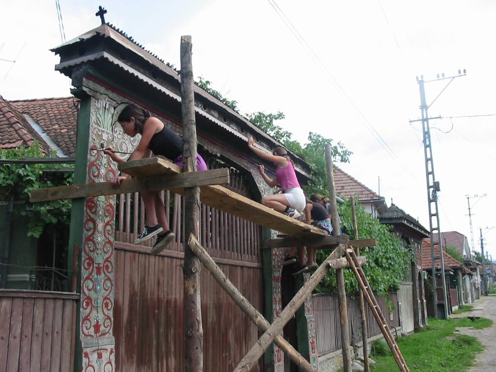Tutaj ciekawe zdjęcie przedstawiające renowację bramy. Cieszy fakt, że zajmują się tym młodzi ludzie. Znaczy, że tradycja jest wciąż żywa. Źródło: www.marefalva.ro